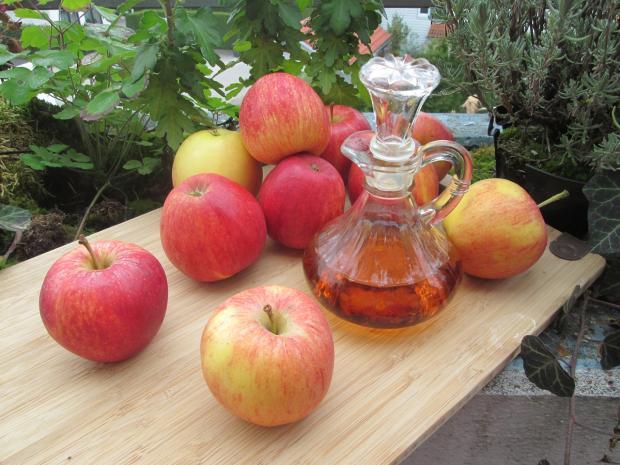 на столе находятся яблоки и яблочный уксус в бутылке