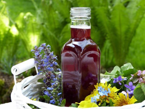 в белой корзинке цветы и бутылка уксуса