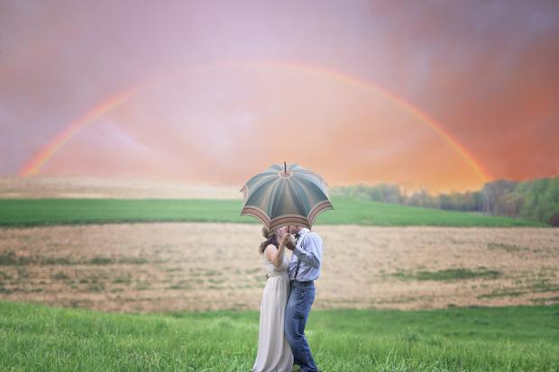 парень и девушка целуются под зонтиком, радуга