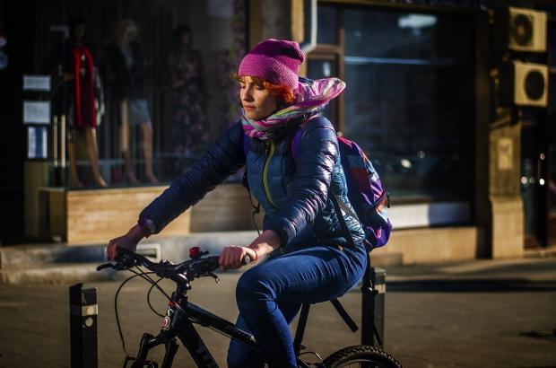 девушка едет по городу на велосипеде
