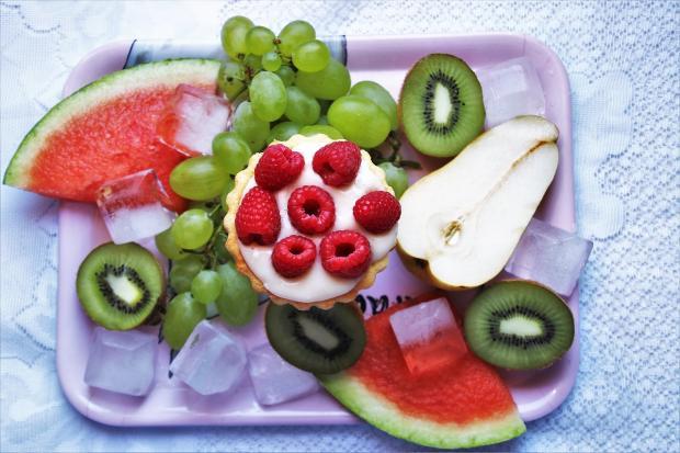 на продолговатом блюде лежат нарезанные фрукты с ягодами и кубиками льда