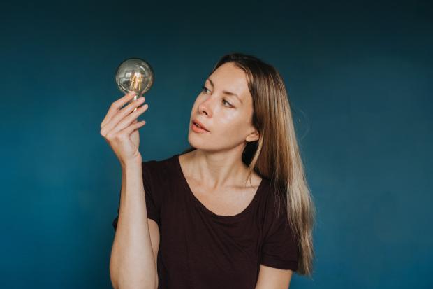 женщина держит в руке горящую лампочку