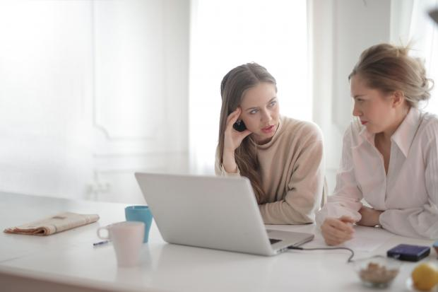 две девушки разговаривают перед ноутбуком