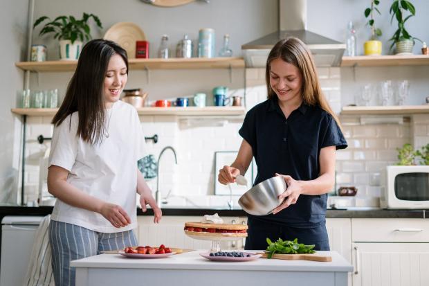 две девушки готовят торт