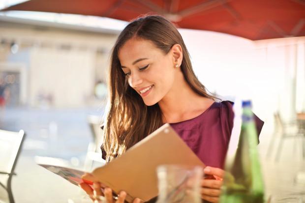 Девушка держит меню в ресторане