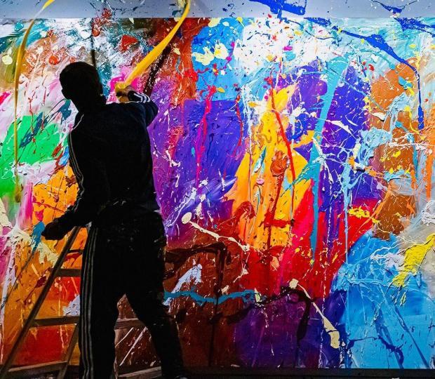 Художник возле яркой картины