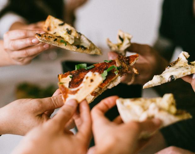 люди держат пиццу в руках
