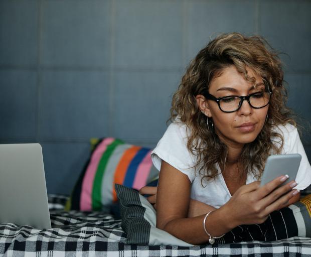 женщина на кровати смотрит в телефон
