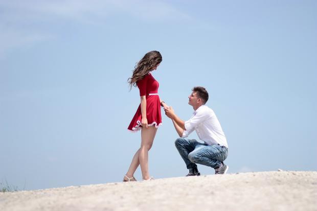 парень стоит на колене пепреед девушкой