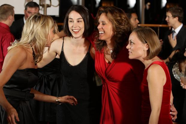 девушки в нарядных платьях разговаривают и смеются на вечеринке