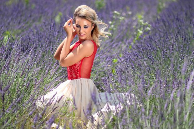 блондинка в красном топе стоит среди лавандового поля
