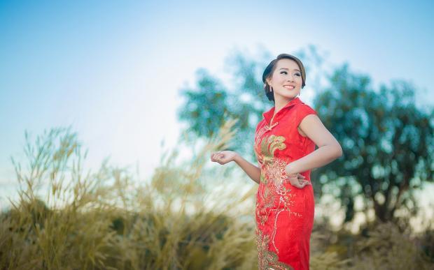 девушка в красном платье стоит в поле