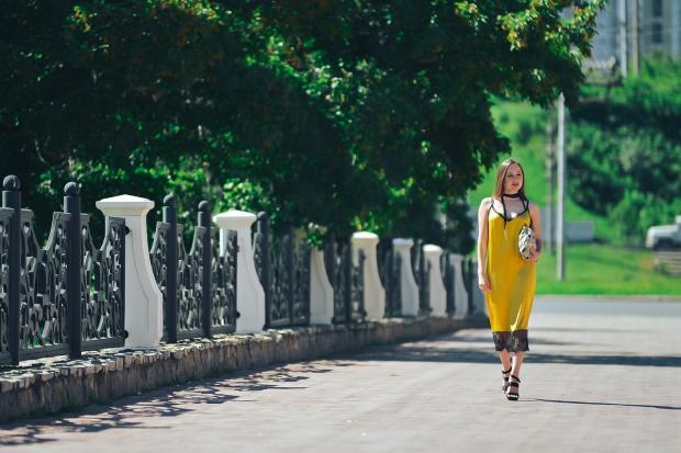 девушка в желтом сарафане идет по городскому тротуару