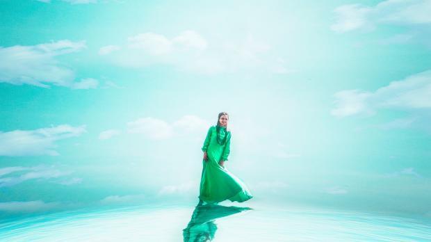 девушка в длинном зеленом платье стоит на фоне голубого неба
