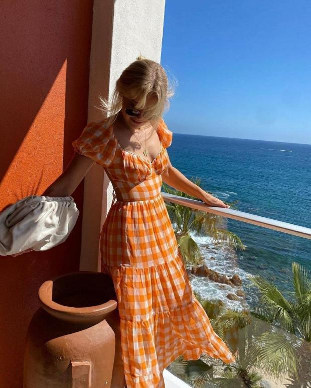 девушка к клетчатом оранжевом платье стоит на балконе дома у моря