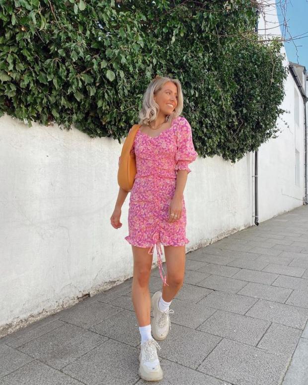 идет девушка в розовом платье и белых кроссовках