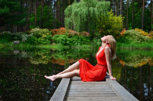 девушка в красном платье сидит на причале