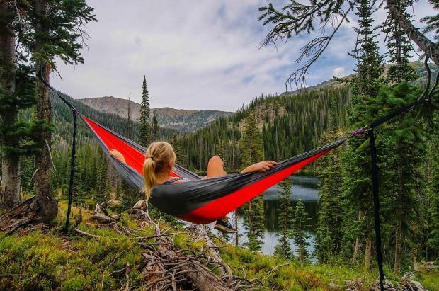 девушка в черно-красном гамаке отдыхает у реки