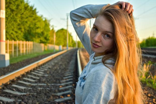 рыжеволосая девушка стоит у железной дороги