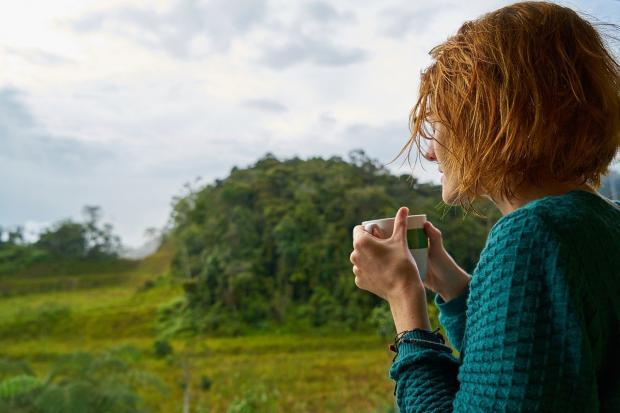 рыжеволосая девушка с короткой стрижкой пьет кофе на природе