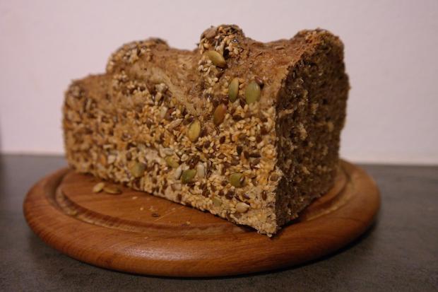 на круглой деревянной подставке лежит буханка цельнозернового хлеба