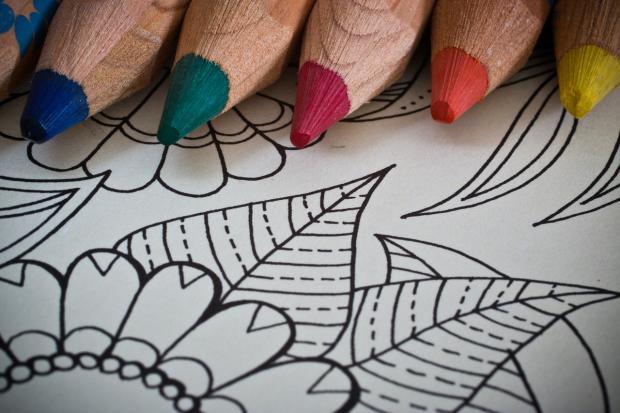 цветные карандаши лежат на раскраске