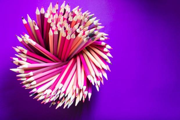 много розовых карандашей на фиолетовом фоне