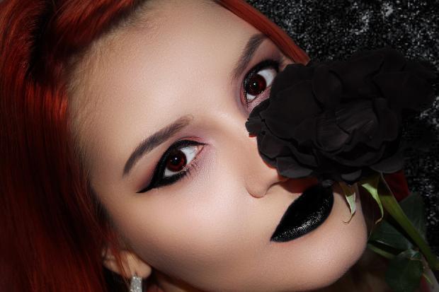 рыжеволосая девушка держит черную розу