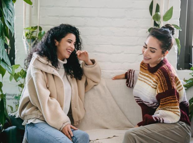 Две девушки разговаривают сидя на диване