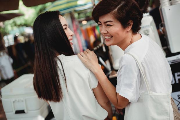 девушки в белых футболках разговаривают и смеются