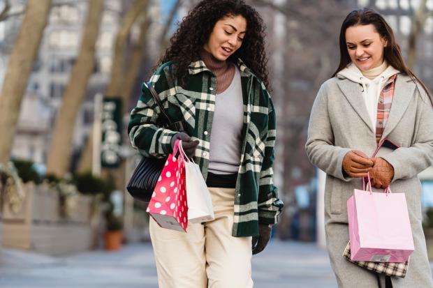 две молодые девушки идут по улице и общаются