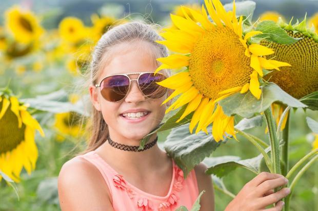 девушка смеется радом с желтым подсолнухом