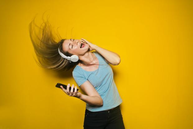 девушка в серой футболке и наушниках на желтом фоне