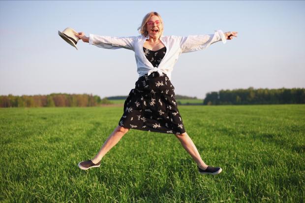 девушка подпрыгивает на траве