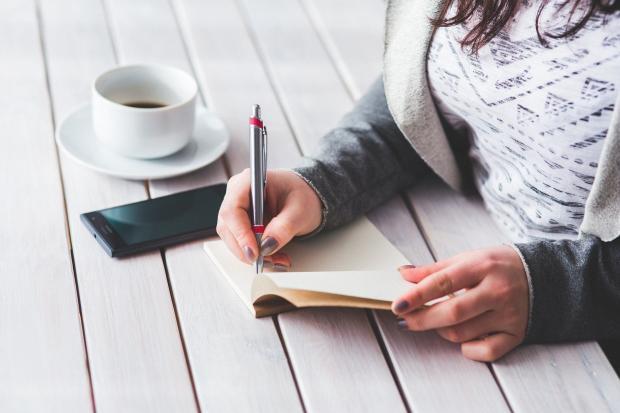 девушка что-то пишет в блокнот, чашка кофе