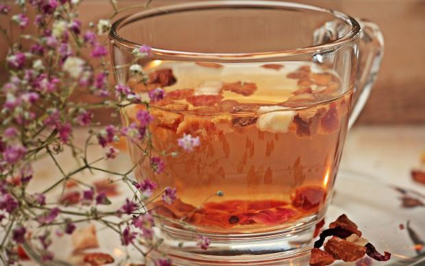 стоит прозрачная кружка травяного чая