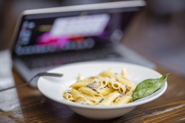тарелка макарон стоит на столе перед ноутбуком