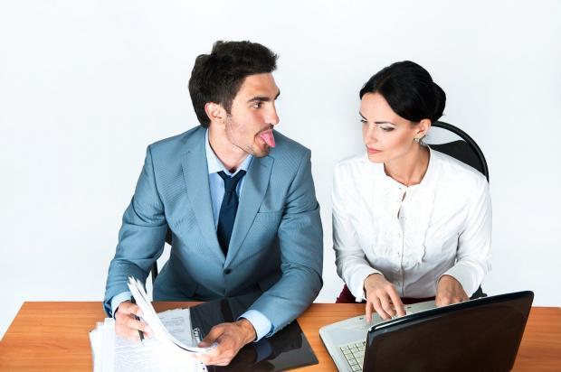 мужчина коллега в офисе показывает девушке за ноутбуком язык