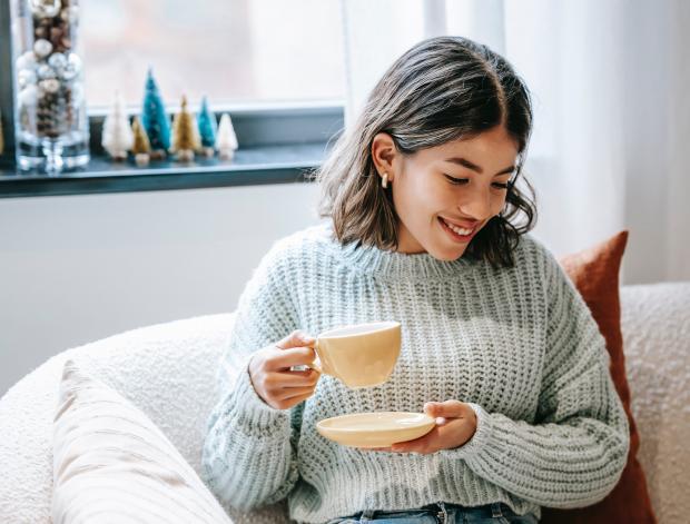 девушка в сером свитере с чашкой чая