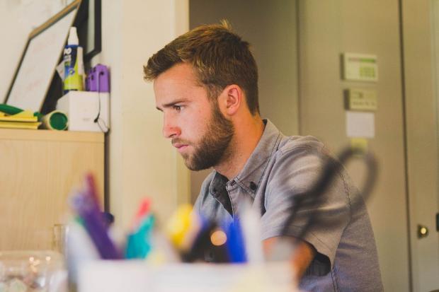 мужчина сидит в офисе за рабочим стлом