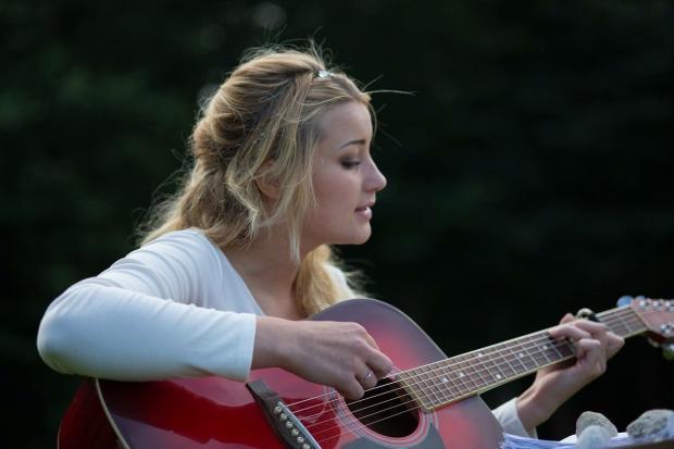 блондинка играет на красной гитаре