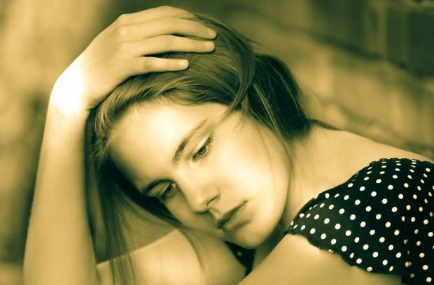 девушка грустно держится за голову
