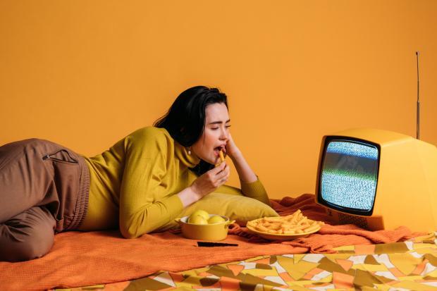 девушка в яркой одежде ест картошку перед телевизором