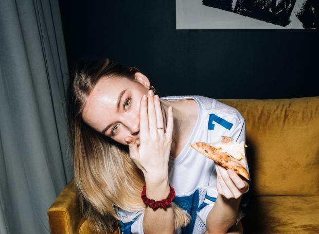 девушка в белой футболке ест пиццу
