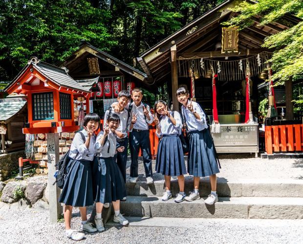 стоят японские школьники в форменной одежде