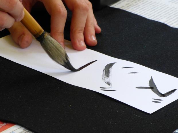 японец пишет иероглифы
