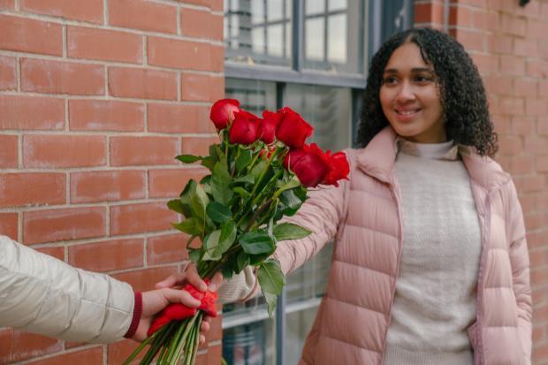 красивой брюнетке с вьющимися волосами дарят букет красных роз