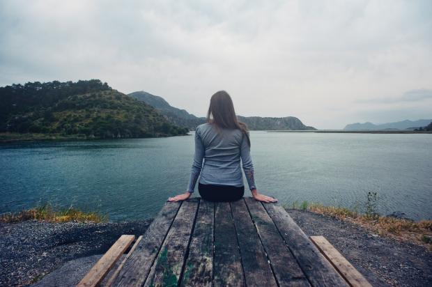 девушка сидит на деревянных мостках и смотрит вдаль на воду