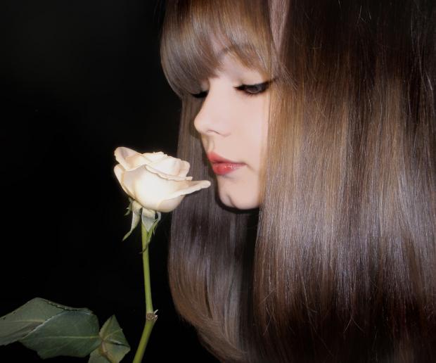красивая девушка нюхает белую розу