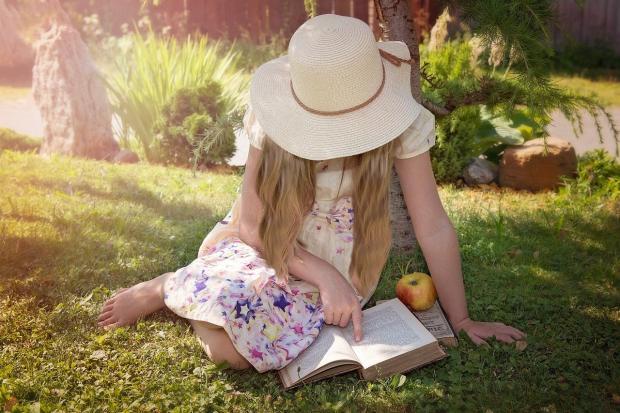 девочка в соломенной шляпке читает книгу сидя на земле
